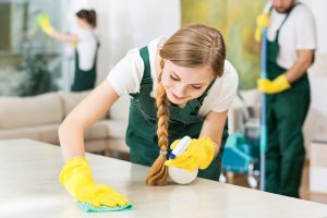 Smiling cleaning lady in yellow rubber gloves during work